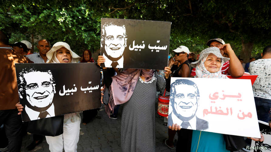 Supporters of presidential candidate Nabil Karoui, hold his pictures as they take part in a rally asking for his release from prison, in front of the courthouse in Tunis, Tunisia, Sept. 3, 2019.