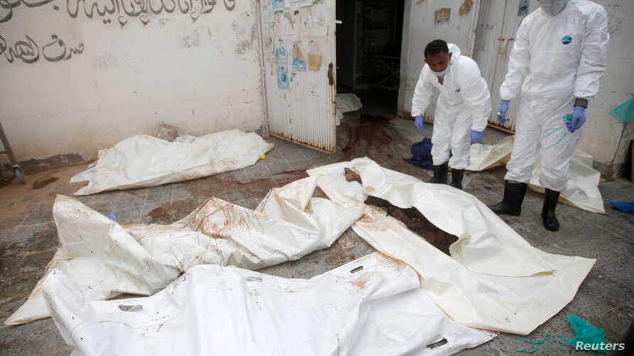 Workers pull bags containing bodies of victims of Saudi-led airstrikes on a Houthi detention center, at a hospital morgue in Dhamar, Yemen, Sept. 2, 2019.