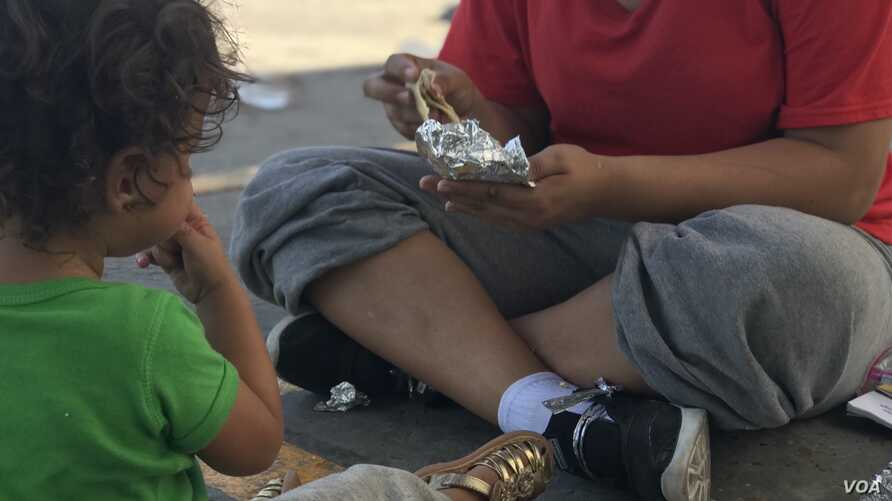 A Honduran woman and her 18-month-old daughter share lunch hours after being dropped off in Nuevo Laredo, Mexico, under the Migrant Protection Protocols, Aug. 8, 2019.