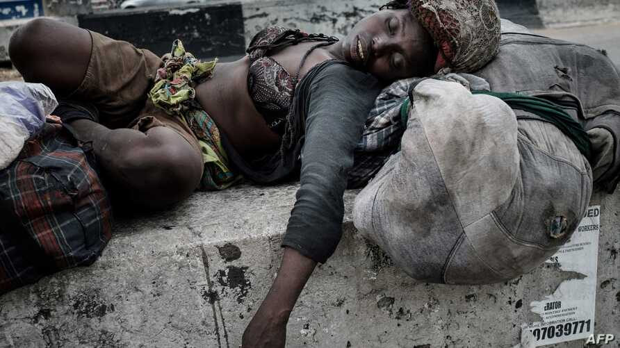 A homeless woman sleeps under a pedestrian bridge in Port Harcourt, southern Nigeria, on February 22, 2019, a day before…