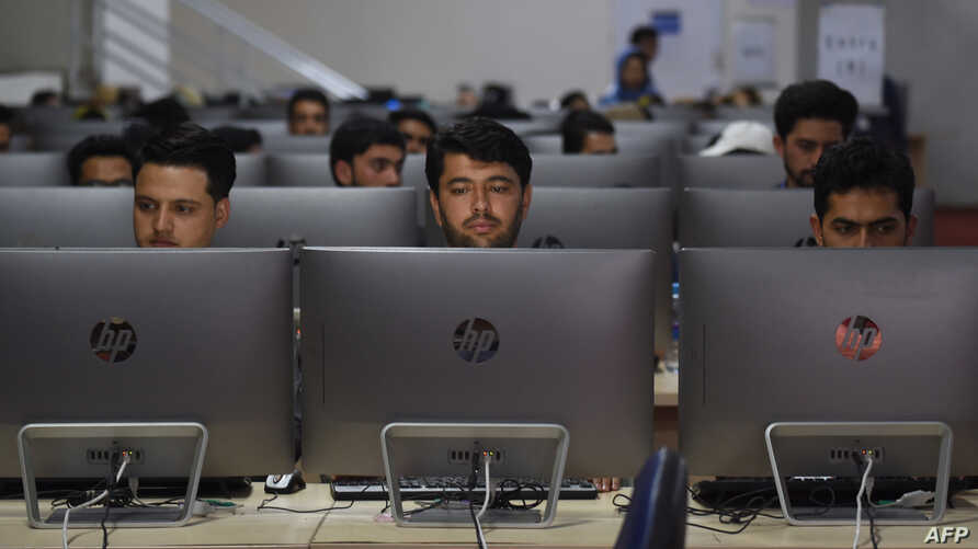 Independent Election Commission (IEC) workers sit at a computer terminal while election information from all over the country…