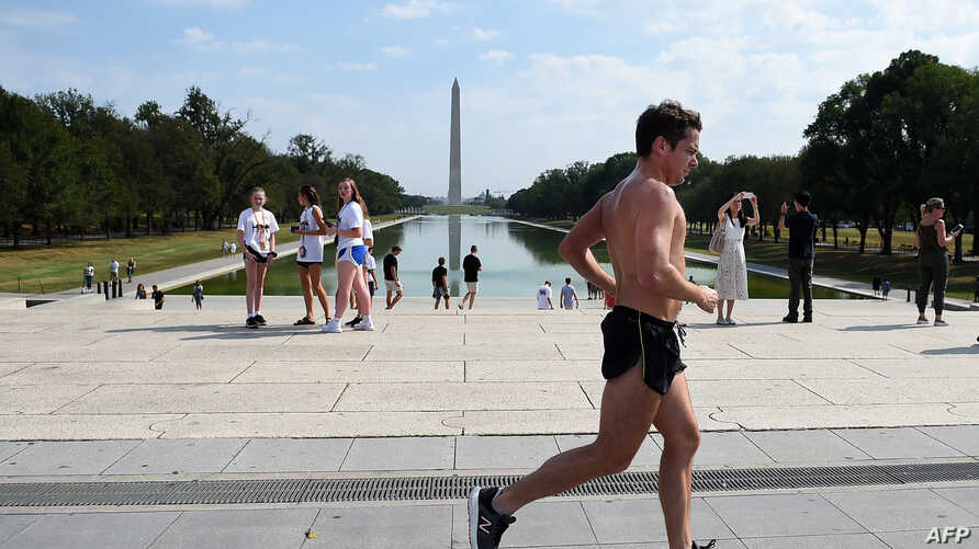 A man runs pass the Lincoln Memorial on the National Mall as temperatures hit 97 degrees Fahrenheit (36 Celsius) in Washington, Oct. 2, 2019.