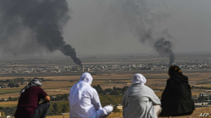 People look on as smoke rises from the Syrian town of Ras al-Ayn.