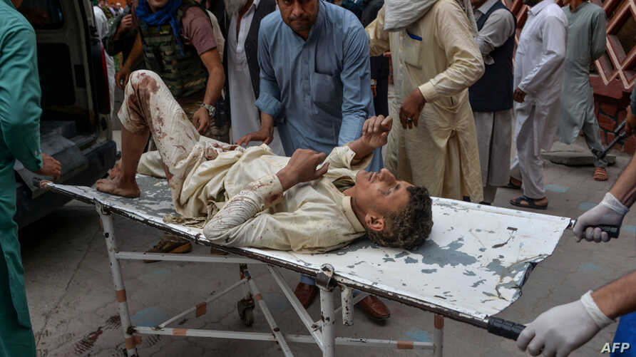 Volunteers carry an injured man on a stretcher to a hospital, following a bomb blast in Haska Mina district of Nangarhar…