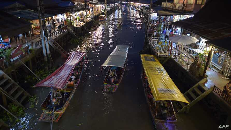 This picture taken on March 28, 2015 shows boats carrying visitors along the Amphawa canal, a small tributary of the Mae Khlong…