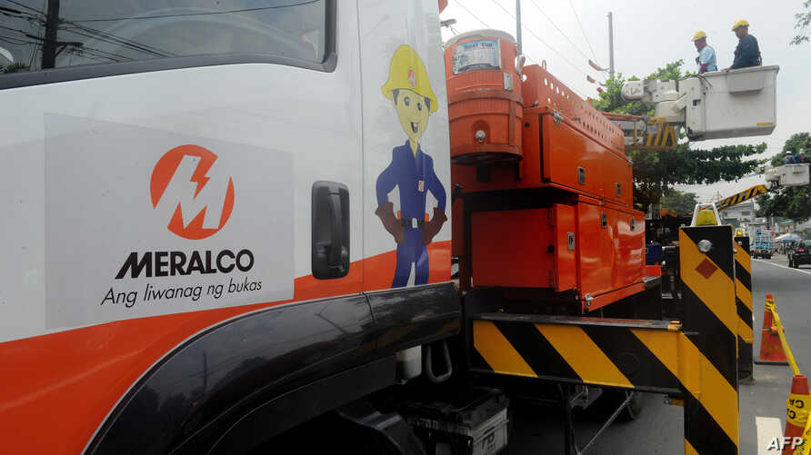 Electricians from the Manila Electric Railroad And Light Company (MERALCO) ready to maintain a secondary transmission line in…