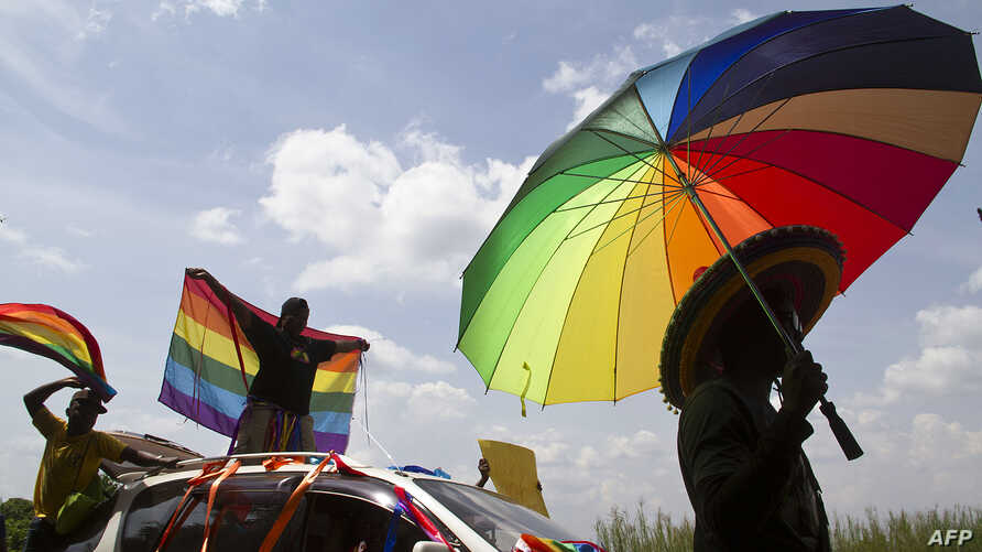 A person holds an umbrella bearing the colors of the rainbow flag as others wave flags during the the first gay pride rally…