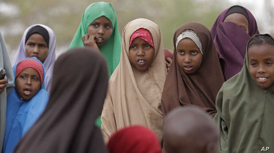Children look at a child, unseen, as he  reacts after being vaccinated at the town of  Liboi, Kenya, Wednesday, July 27, 2011…