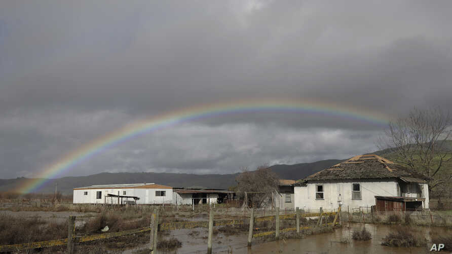 A rainbow is seen over a flooded landscape Wednesday, Jan. 11, 2017, in Hollister, Calif. Forecasters said rain and snow would…
