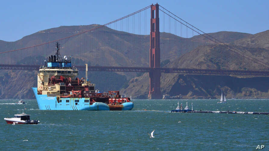 FILE - A ship tows the Ocean Cleanup Project's first buoyant trash-collecting device toward the Golden Gate Bridge in San Francisco en route to the Pacific Ocean, Sept. 8, 2018.