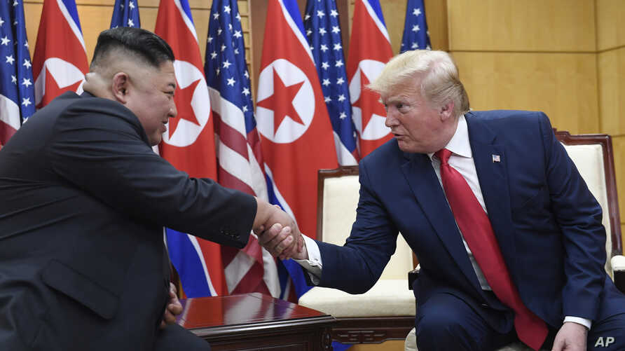 FILE - In this June 30, 2019, file photo, U.S. President Donald Trump, right, meets with North Korean leader Kim Jong Un at the…