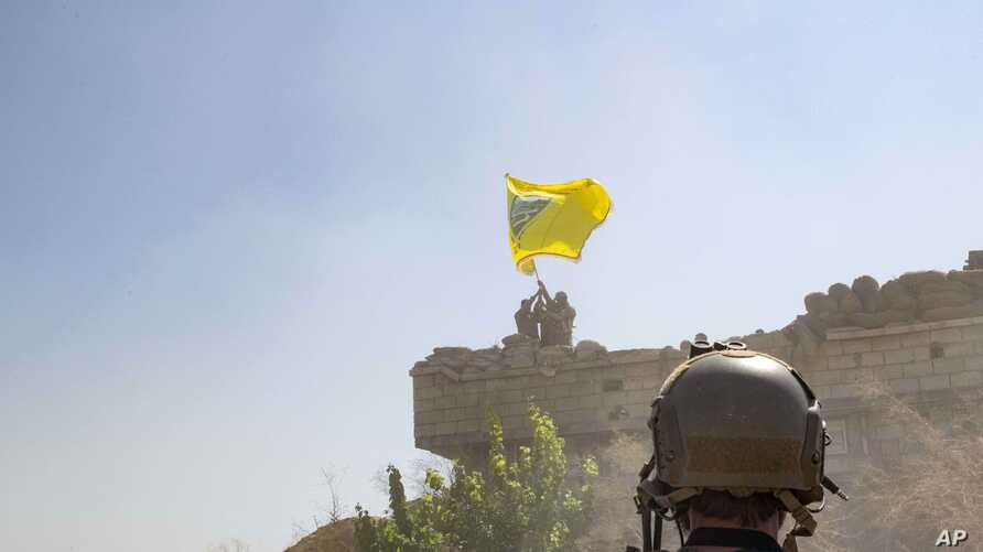 In this Sept. 21, 2019, photo, released by the U.S. Army, a U.S. soldier oversees members of the Syrian Democratic Forces as…