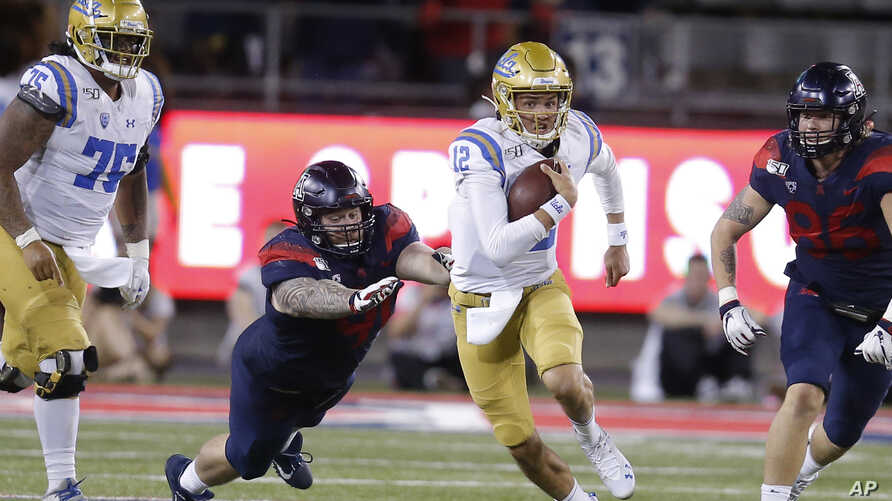 """UCLA quarterback Austin Burton (12) runs during an NCAA college football game against Arizona, Sept. 28, 2019. A bill signed Monday in California will allow student athletes to use their """"name, image, or likeness"""" to earn compensation."""