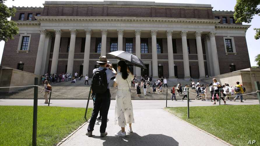 FILE - People stop to record images of Widener Library on the campus of Harvard University in Cambridge, Mass., July 16, 2019.