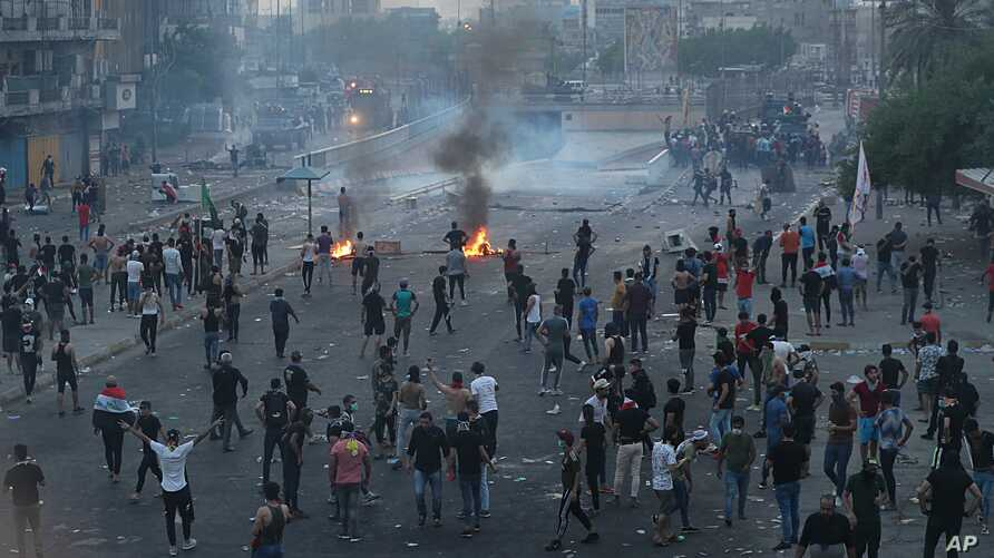 Anti-government protesters set fires and block roads while security forces fire tear gas during a protest in Baghdad, Iraq, Oct. 2, 2019.