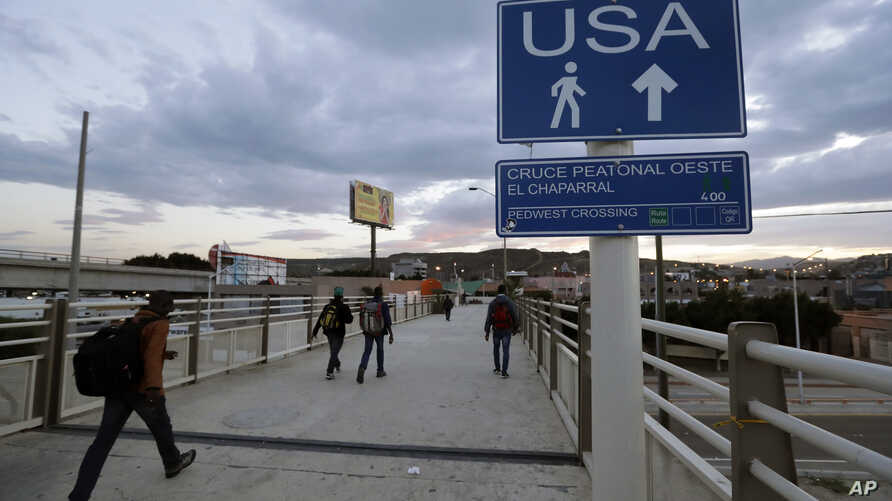 FILE - In this Sept. 27, 2016 file photo, Haitians make their way towards the border crossing in Tijuana, Mexico. The Trump administration is planning to expand the collection of DNA from migrants who cross the U.S. border.