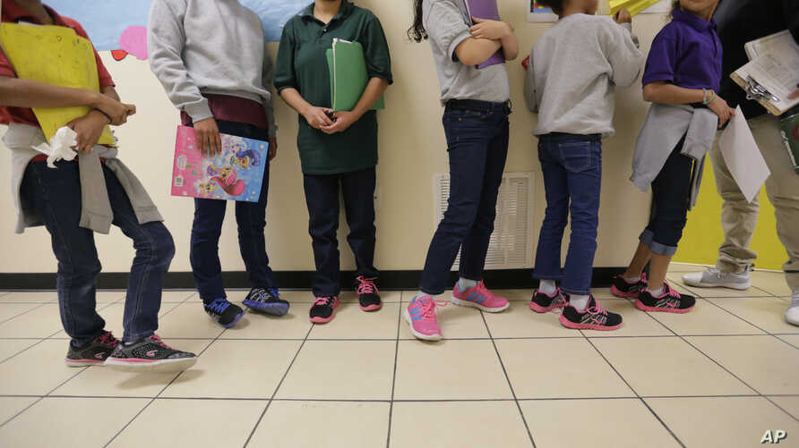 """Migrant teens line up for a class at a """"tender-age"""" facility for babies, children and teens, in Texas' Rio Grande Valley, Aug. 29, 2019, in San Benito, Texas."""