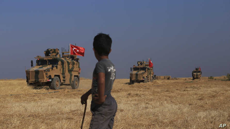 "Turkish armored vehicles conduct a joint ground patrol with American forces in the so-called ""safe zone"" on the Syrian side of the border with Turkey, near the town of Tal Abyad, northeastern Syria, Oct. 4, 2019."