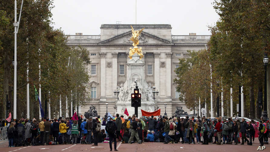 Climate protestors block the Mall leading to Buckingham Palace, rear, central London, Oct. 7, 2019.