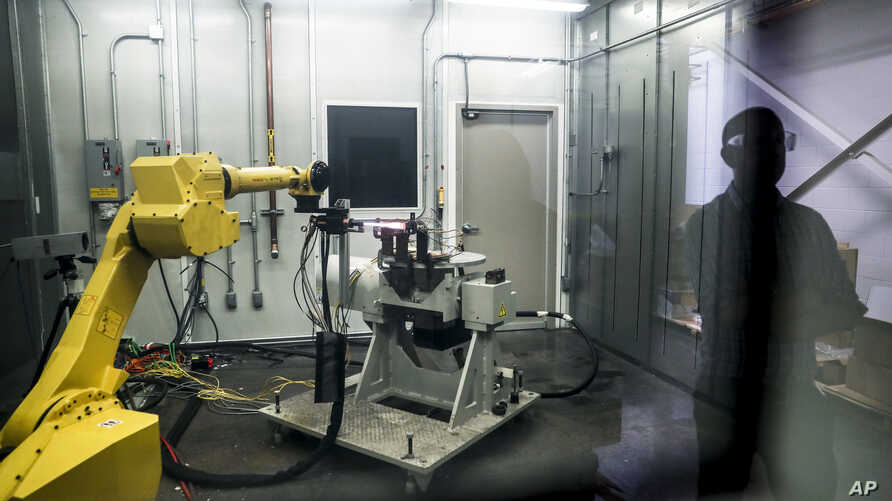 FILE - A robotic arm with a high-intensity blowtorch is remotely operated to test ceramic matrix composites, which make engines more durable, heat-resistant and efficient, at the General Electric Aviation plant in Evendale, Ohio.