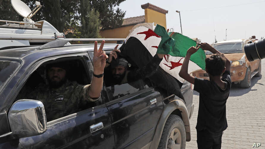 Members of Turkey-backed Syrian National Army (former FSA) flash the V-sign as they drive back to Turkey near the border between Turkey and Syria, in Akcakale, Sanliurfa province, southeastern Turkey, Oct. 9, 2019.