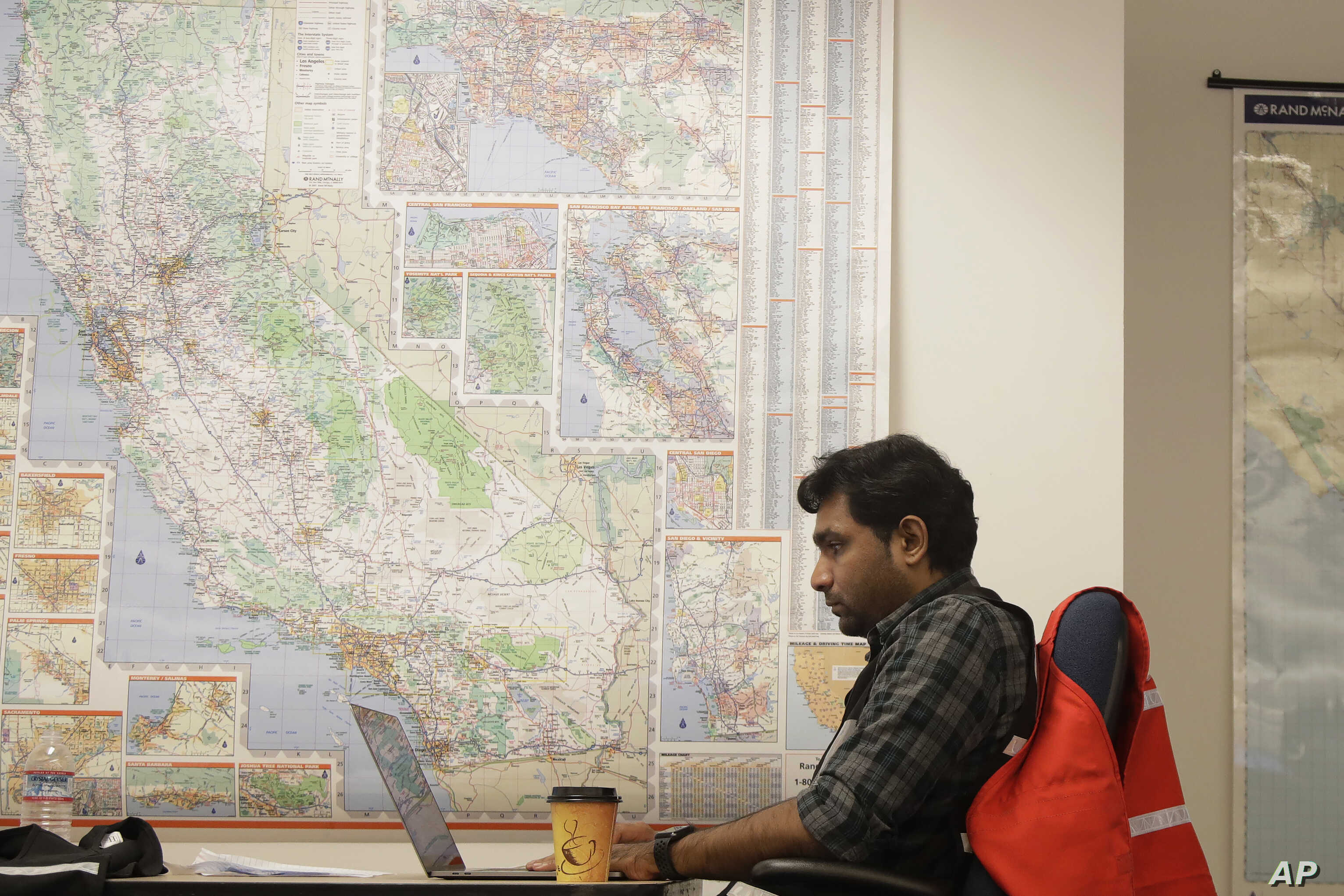 Senior program analyst Siva Jasti works next to a map of California in the Pacific Gas & Electric (PG&E) Emergency Operations…