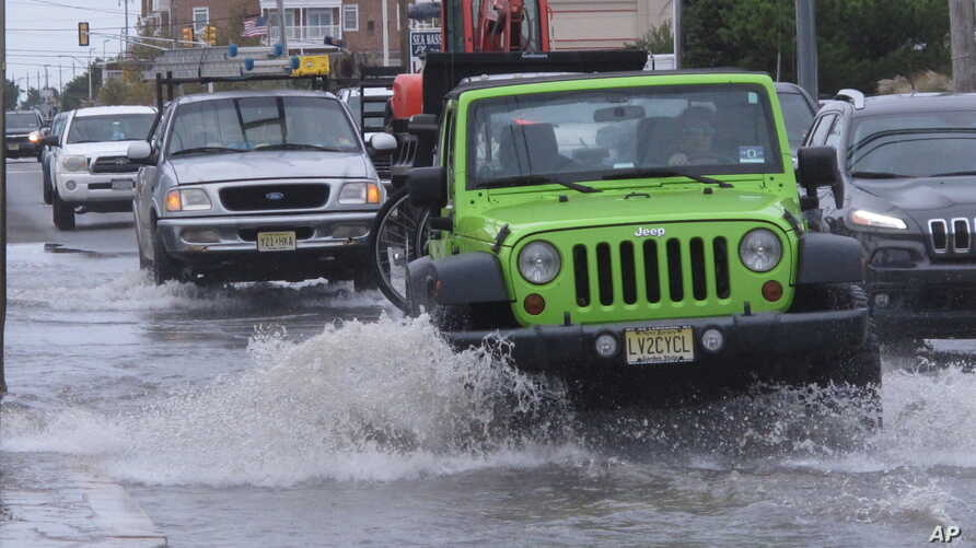 Cars drive through a flooded road at the entrance to Long Beach Island in Ship Bottom, N.J. on Oct. 11, 2019.