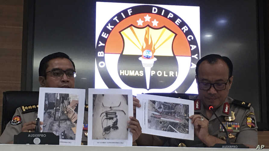 At a press conference in Jakarta, Indonesian National Police spokesperson Brig.Gen. Dedi Prasetyo, right, and an aide show photos of evidence of confiscated items during raids following a knife attack against an Indonesian official, Oct. 14, 2019.