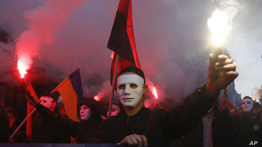 Members of the nationalist movements light flares during a rally marking Defense of the Homeland Day in center Kyiv, Ukraine,…