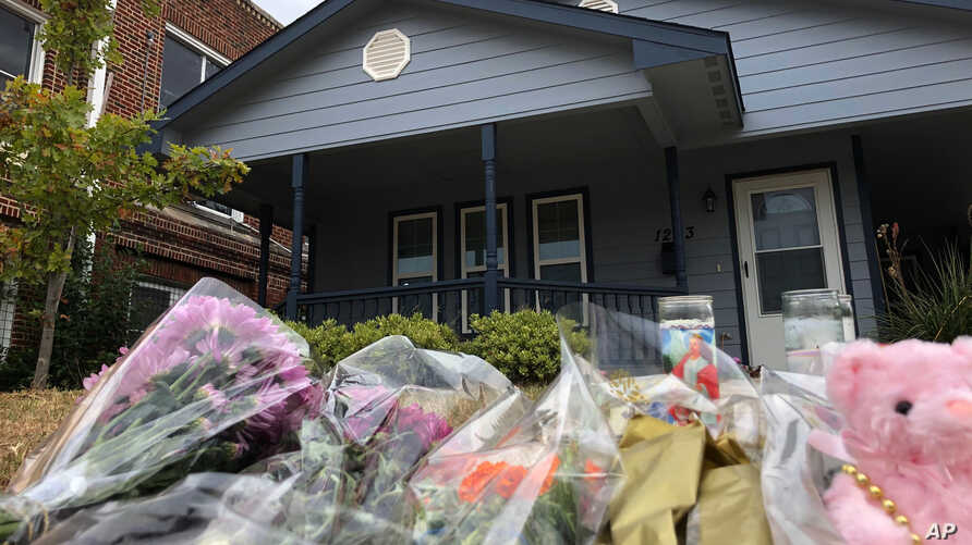 Bouquets of flowers and stuffed animals are piling up outside the Fort Worth home Monday, Oct. 14, 2019, where a 28-year-old…