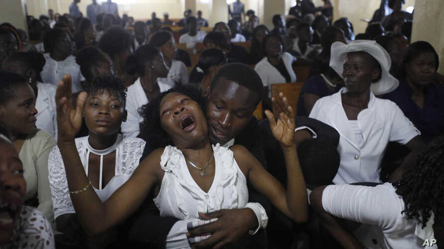 """Relatives of murdered community leader Josemano """"Badou"""" Victorieux mourn during Victorieux's funeral in Port-au-Prince, Haiti."""