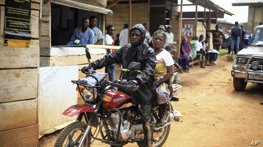 Motorcycle taxi driver Germain Kalubenge transports a woman whose 5-year-old daughter had a fever and was vomiting to an Ebola…