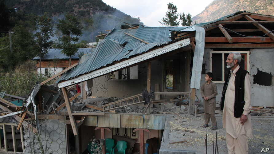 Pakistani Kashmiri residents look at the destruction reportedly caused by artillery fired by Indian forces in Neelum Valley along the Line of Control in Pakistani Kashmir, Oct. 21, 2019.