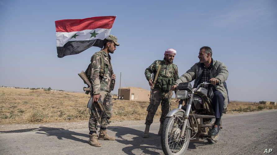 Syrian government forces man a checkpoint near the town of Tal Tamr, north Syria, Tuesday, Oct. 22, 2019. Russia and Turkey…