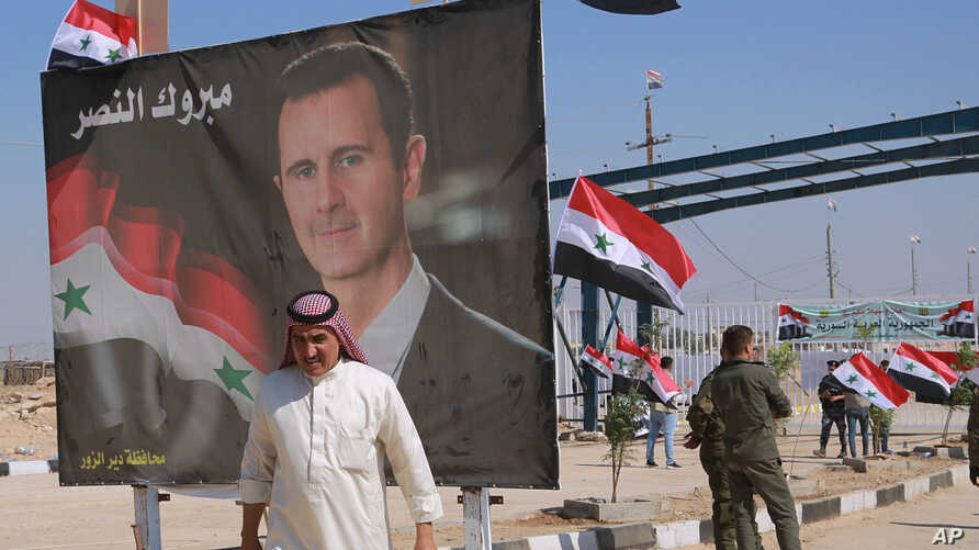 FILE - In this Sept. 30, 2019, file photo, a man passes a poster of Syrian President Bashar Assad with Arabic that reads, …