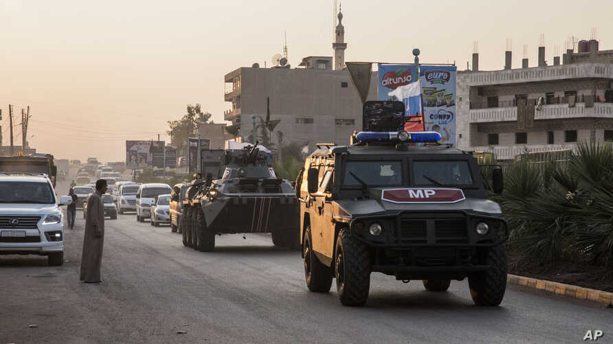 Russian forces patrol in the city of Amuda, north Syria, Thursday, Oct. 24, 2019. Syrian forces, Russian military advisers and…