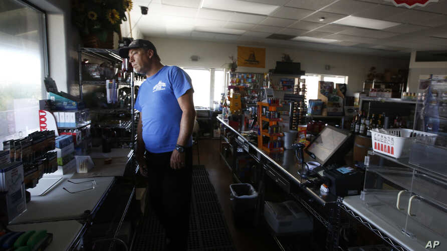 Brian Boyd peers out the window of the darkened Clear Creek Crossing store near Paradise, Calif., Thursday, Oct. 24, 2019. The…
