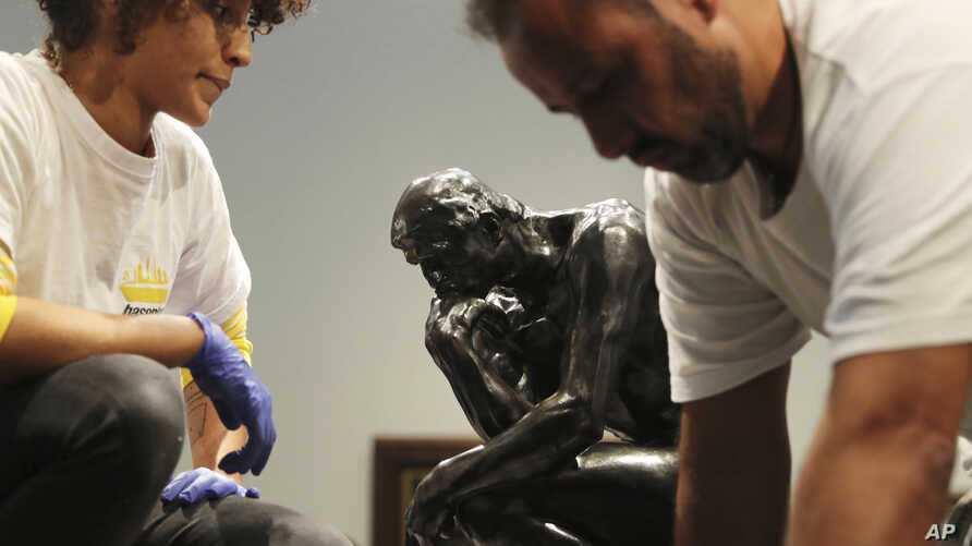Staff members prepare to move Rodin's The Thinker bronze statue during installation at the Louvre Museum in Abu Dhabi, United Arab Emirates, Oct. 27, 2019. The statue created in the 1880s is a one-year loaner from Rodin Museum in France.