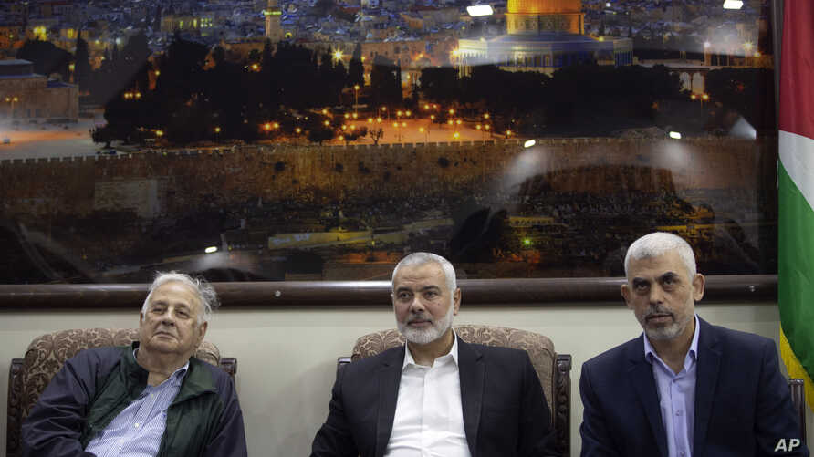 Hamas leader in the Gaza Strip Yahya Sinwar, right, sits with the movement chief, Ismail Haniyeh, center, as they meet the Head of the Central Elections Commission, Hanna Nasser, in Gaza City, Oct. 28, 2019.