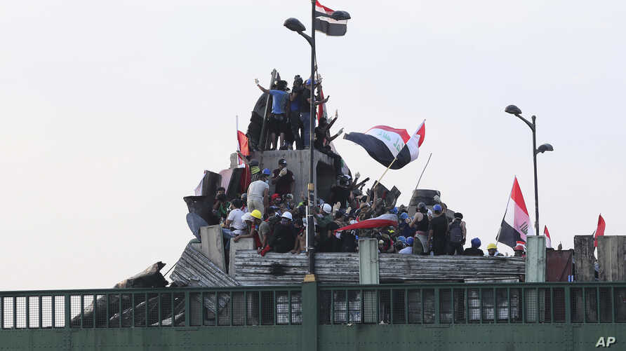 Anti-government protesters control the barriers set by Iraqi security forces to close the bridge leading to the Green Zone…