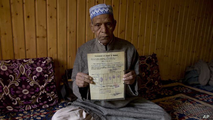 "Ghulam Mohammad Zargar, an elderly Kashmiri man shows his domicile document locally know as ""State Subject"" which was only held by permanent residents of Jammu and Kashmir in Srinagar, Indian controlled Kashmir, Oct. 31, 2019."