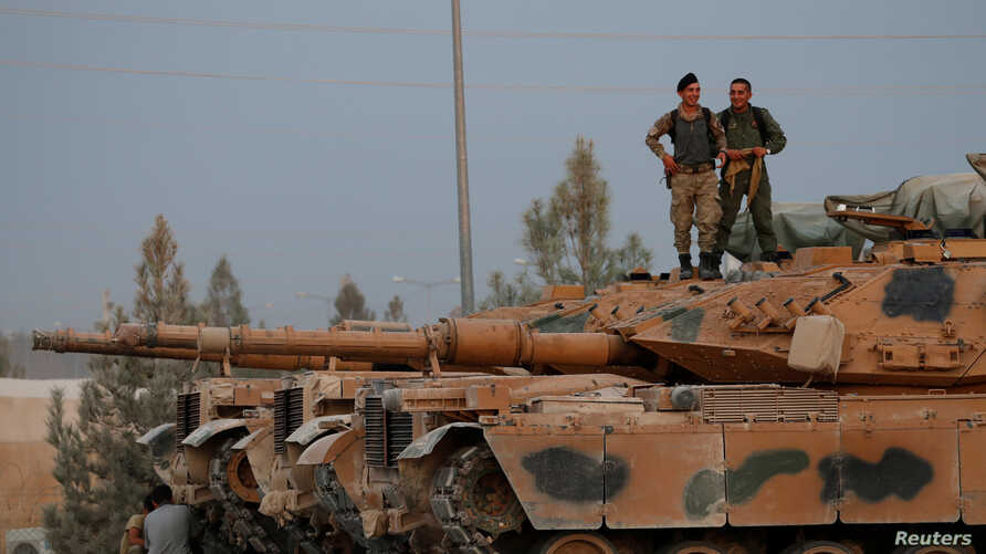 Turkish soldiers stand on top of a tank in the border town of Akcakale in Sanliurfa province, Turkey, October 11, 2019. REUTERS…