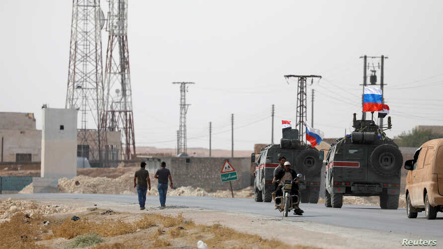 Russian and Syrian national flags flutter on military vehicles near Manbij, Syria October 15, 2019. REUTERS/Omar Sanadiki -…