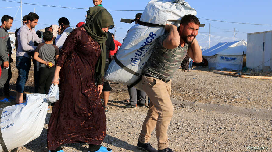 Syrian displaced families, who fled violence after the Turkish offensive in Syria, receive aid in Bardarash refugee camp on the…