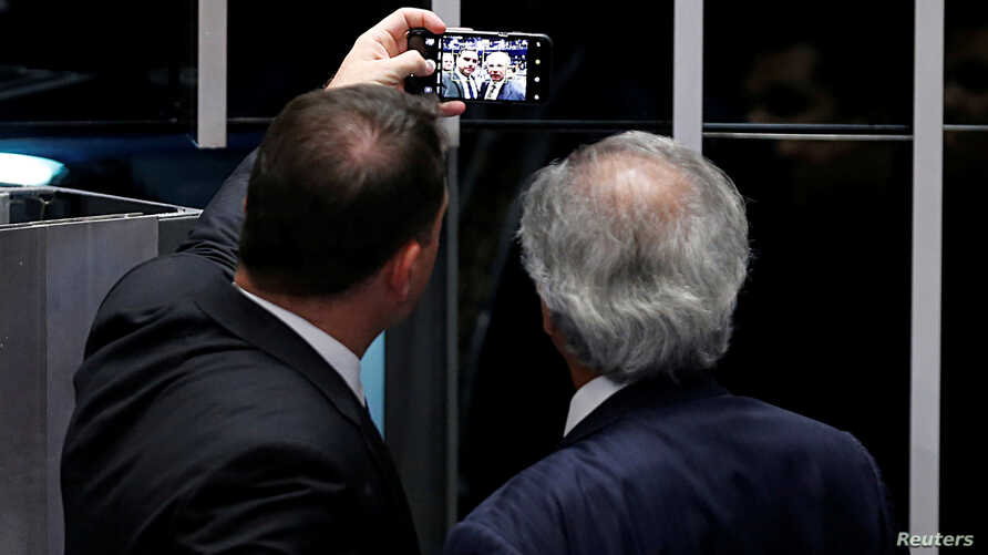 Brazil's Financial Minister Paulo Guedes takes a photo with Senator Flavio Bolsonaro following the promulgation of the vote on…