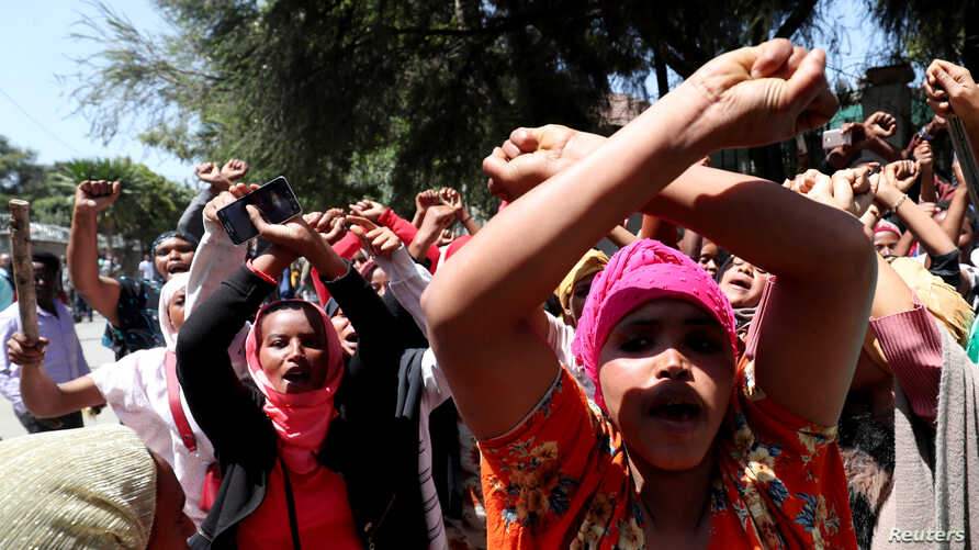 Women supporters show the Oromo protest gesture outside Jawar Mohammed's house, an Oromo activist and leader of the Oromo…