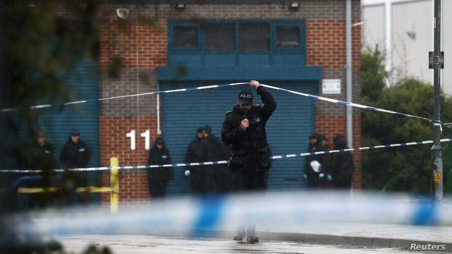 A police officer moves the tape inside the cordon, at the scene where bodies were discovered in a lorry container, in Grays,…