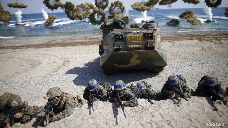 South Korean (blue headbands) and U.S. Marines take positions as amphibious assault vehicles of the South Korean Marine Corps…