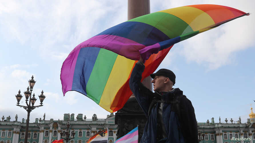 FILE - A participant waves a rainbow flag during an LGBT community rally in central Saint Petersburg, Russia, Aug. 3, 2019.