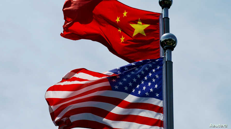 FILE PHOTO: Chinese and U.S. flags flutter near The Bund, before U.S. trade delegation meet their Chinese counterparts for…